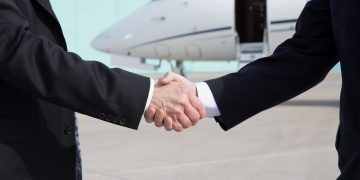 Business people shaking hands in front of a corporate jet